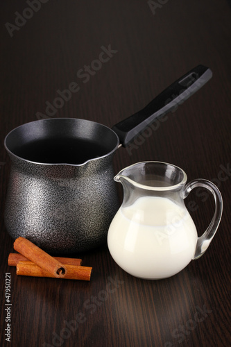 Coffee maker and milk on brown table
