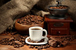 Coffee grinder and cup of coffee on burlap background