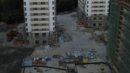 Workers walk on building site in housing estate below