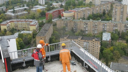 Workers mount protection on new building roof on housing estate