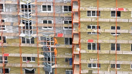 Workers stands on scaffold put window frame and glaze windows
