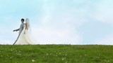 couple in wedding dresses walks keeping for hands