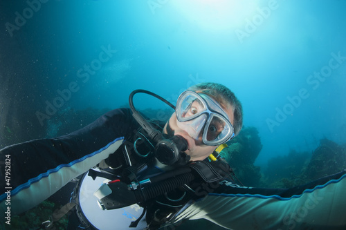 A scuba diver gone crazy try to open porthole from underwater