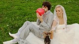 groom inflates red air sphere-heart and gives to bride