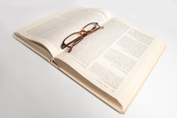 book with glasses isolated on white
