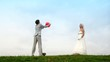 Newly-married couple on meadow throws each other