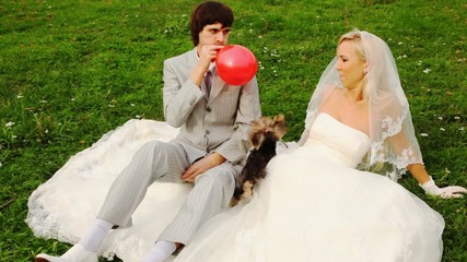 groom inflates sphere-heart and gives to its bride, and dog