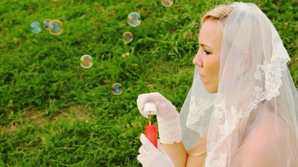 bride in white starts up soap bubbles