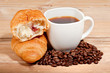 Croissant with coffee and beans on wooden background
