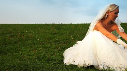 bride one sits on grass on slope of hill and corrects dress