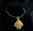 golden necklace with pendant decorated by gemstone