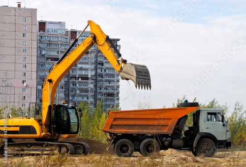 Excavator loads the ground in a truck on a background of houses
