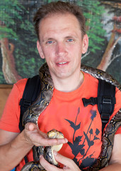 Portrait of the man with boa (snake) on shoulders