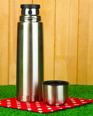 metal thermos on grass on wooden background