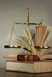 Gold scales of justice and books on grey background