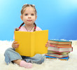 cute little girl with colorful books, on blue background