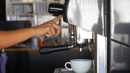 Barista making single espresso shot in white mug