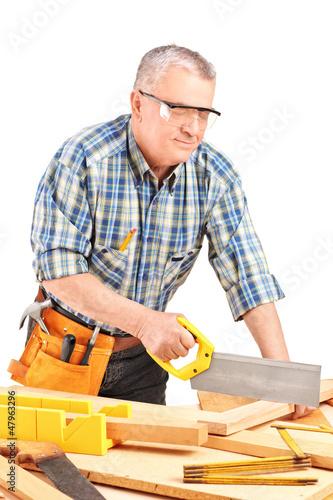 Carpenter cutting wooden batten with a saw
