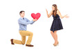 Smiling male kneeling with red heart and surprised woman
