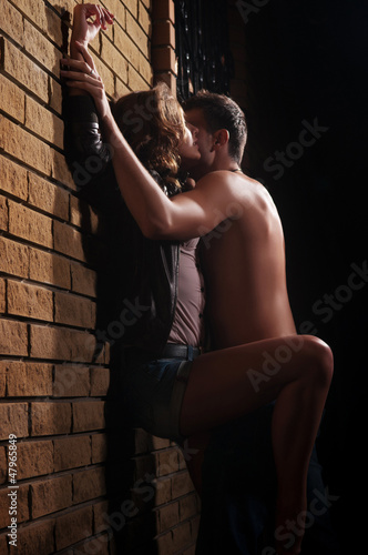 guy kissing his girlfriend against a wall at home