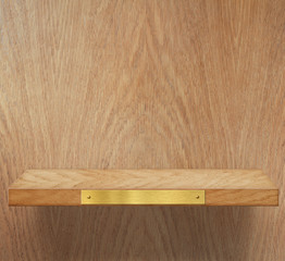 Empty wooden shelf with brass metal plate