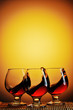 Three glasses of cognac on yellow background with splash