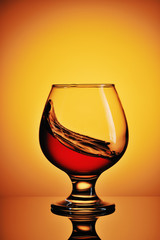 Glass of cognac on yellow background