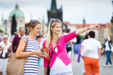 Fototapety Two female tourists walking along the Charles Bridge while sight
