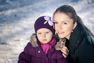 Young mother and her baby girl on a snowy winter day