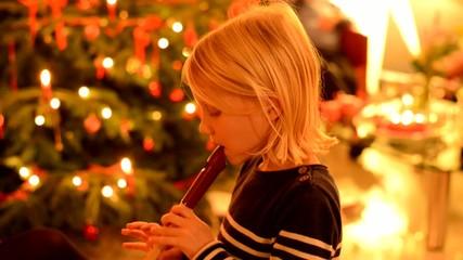 Kleines Mädchen spielt Blockflöte vor Christbaum