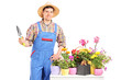 Male gardener holding a spade and posing next to a table
