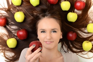 Beautiful young woman eating an apple. Isolated over white.