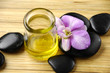 bottle of aromatherapy oil and black stones with orchid
