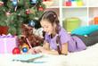 Little girl writing letter to Santa near christmas tree