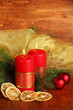 Two candles and christmas decorations, on wooden background