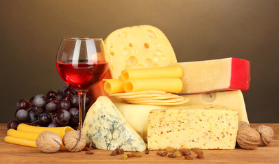 Various types of cheese on wooden table on brown background