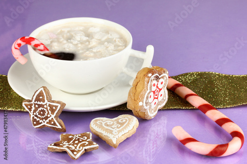Cup of coffee with Christmas sweetness on purple background