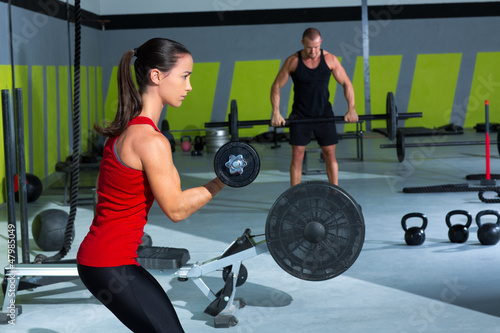 girl dumbbell and man weight lifting bar workout