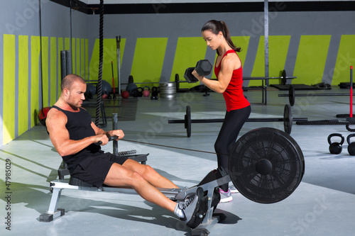 Gym couple with dumbbell weights and fitness rower