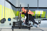 Crossfit sled push man pushing weights workout