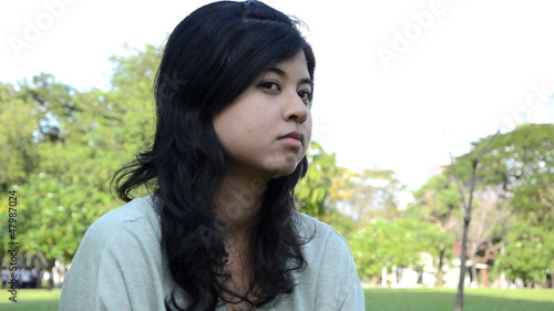 Young, sad, lonely beautiful woman face in the park