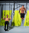 Crossfit dip ring two men workout at gym dipping
