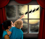 Woman with child pointing at Santa Claus on sky