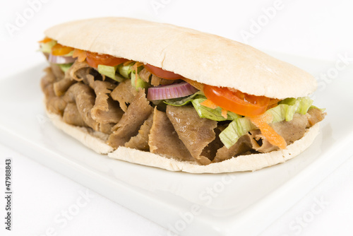 Donner meat with salad in a flatbread on a white background.
