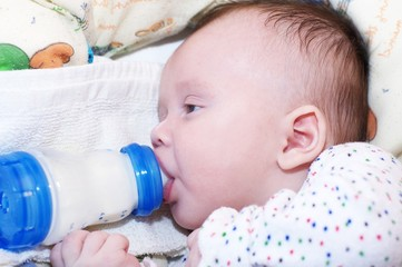 The baby eats from a small bottle (3 months)
