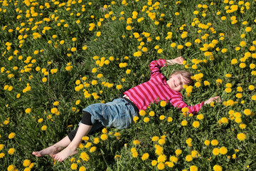 Mädchen liegt in einer Blumenwiese