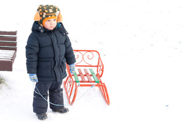 Young boy playing with a sled in snow