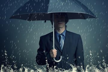 Businessman with an umbrella in the rain.