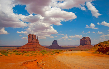 Monument Valley landscape with clouds and dirt road