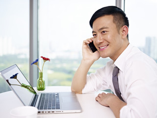 young asian businessman talking on cellphone in office